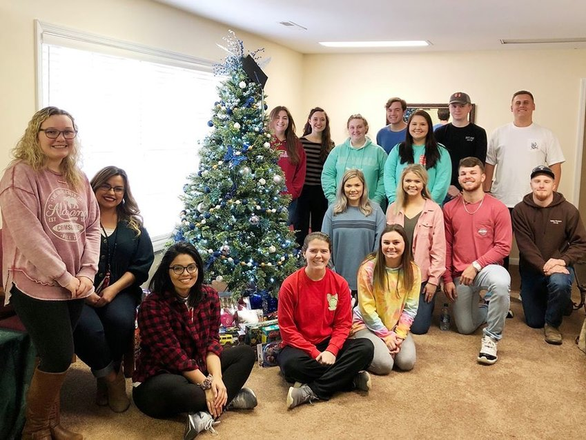 Scholars with the Walker College Foundation surround a Christmas tree with gifts they later wrapped for children in need.