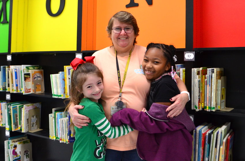 T.R. Simmons custodian Sandy Dickerson always has students greeting her with hugs. She is pictured with students Aubree McCain and Geleha Johnson.