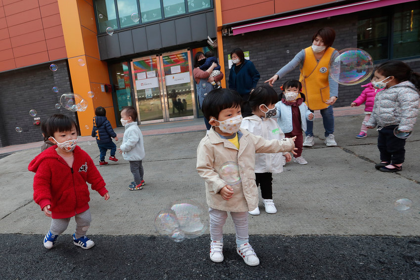 Children wearing face masks to help protect against the spread of the new coronavirus watch soap bubbles fly at the Chogyesa temple in South Korea, Friday, April 24, 2020. (AP Photo/Ahn Young-joon).