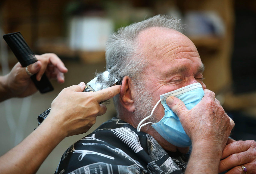 Lonnie Sullivan covers his face with a mask while getting a haircut at The Barber Shop in Broken Arrow, Okla., on Friday, April 24, 2020.  The shop was among several allowed to reopen in a loosening of coronavirus-related restrictions. (Matt Barnard/Tulsa World via AP)