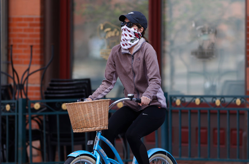 A bicylcist wears face protection against the new coronavirus while pedalling through Laarimer Square early Saturday, April 25, 2020, in downtown Denver. (AP Photo/David Zalubowski).