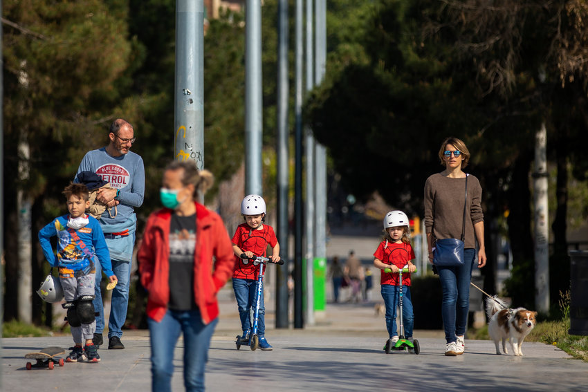 Families with their children walk along a boulevard in Barcelona, Spain, Sunday, April 26, 2020 as the lockdown to combat the spread of coronavirus continues. On Sunday, children under 14 years old will be allowed to take walks with a parent for up to one hour and within one kilometer from home, ending six weeks of compete seclusion. (AP Photo/Emilio Morenatti).