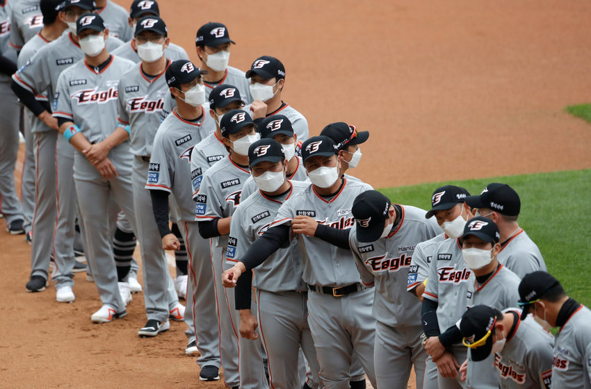 Hanwha Eagles players wearing face masks line up during the start of regular season baseball game between Hanwha Eagles and SK Wyverns in Incheon, South Korea, Tuesday, May 5, 2020. Cheerleaders danced beneath rows of empty seats and umpires wore protective masks as a new baseball season began in South Korea. After a weeks-long delay because of the coronavirus pandemic, a hushed atmosphere allowed for sounds like the ball hitting the catcher's mitt and bats smacking the ball for a single or double to echo around the stadium. (AP Photo/Lee Jin-man)