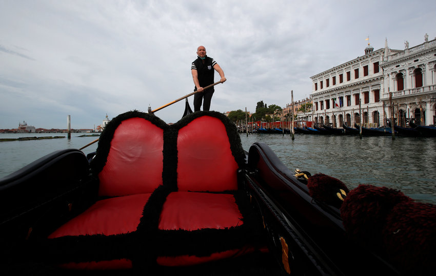 In this picture taken on Wednesday, May 13, 2020, gondoliers President Andrea Balbi sails his gondola at the canal Grande (Grand Canal) in Venice, Italy. Venetians are rethinking their city in the quiet brought by the coronavirus pandemic. For years, the unbridled success of Venice's tourism industry threatened to ruin the things that made it an attractive destination to begin with. Now the pandemic has ground to a halt Italy's most-visited city, stopped the flow of 3 billion euros in annual tourism-related revenue and devastated the city's economy. (AP Photo/Antonio Calanni)