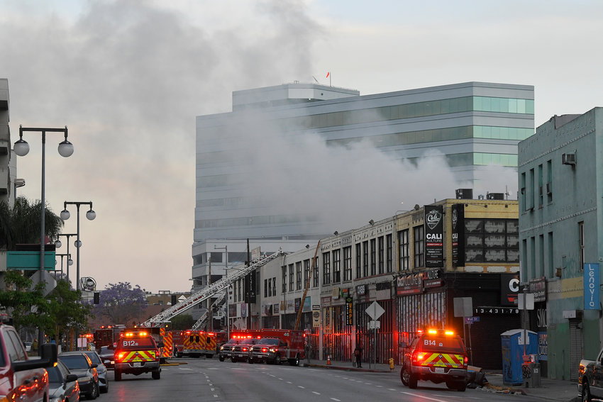 Los Angeles Fire Department firefighters work the scene of a structure fire that injured 10 firefighters according to a fire department spokesman, Saturday, May 16, 2020, in Los Angeles. (AP Photo/Mark J. Terrill)