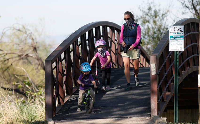 A woman and children wear face coverings while crossing a bridge in Barr Lake State Park Sunday, May 16, 2020, near Brighton, Colo. (AP Photo/David Zalubowski).
