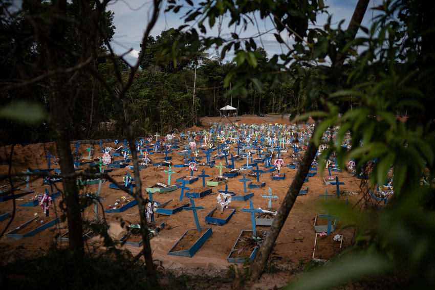 In this May 11, 2020 photo, graves for people who have died in the past month fill a new section of the Nossa Senhora Aparecida cemetery, amid the new coronavirus pandemic, in Manaus, Brazil. Indigenous tribes dwelling up the Solimoes and Negro rivers that merge in Manaus to form the Amazon River tried for weeks to seal their reserves off from the virus, pleading for donations while awaiting government delivery of food assistance so they could remain isolated. It didn't come for many, indigenous advocates said.(AP Photo/Felipe Dana)