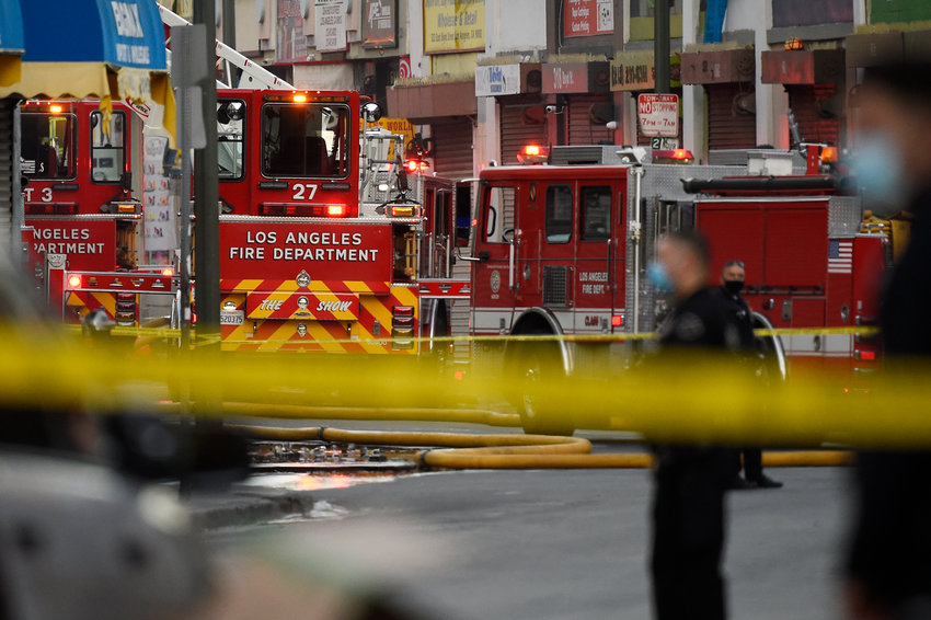 Los Angeles Police Department officers work the scene of a structure fire that injured 10 firefighters according to a fire department spokesman, Saturday, May 16, 2020, in Los Angeles. (AP Photo/Mark J. Terrill)