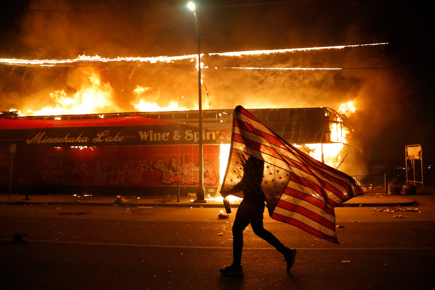 A protester carries the carries the U.S. flag upside, a sign of distress, Thursday, May 28, 2020, in Minneapolis. Violent protests over the death of George Floyd, the black man who died in police custody broke out in Minneapolis for a third straight night. (AP Photo/Julio Cortez)