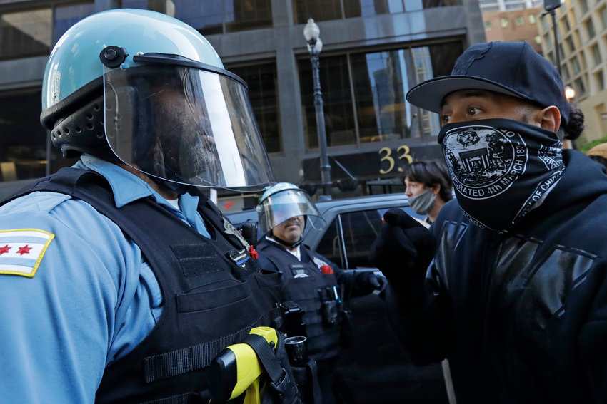 Protesters confront police officers during a protest over the death of George Floyd in Chicago, Saturday, May 30, 2020. Protesters protest in response to George Floyd's death in police custody in Minneapolis on Memorial Day. (AP Photo/Nam Y. Huh)