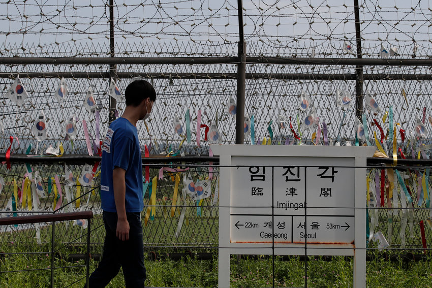 A visitor walks in front of a directional sign showing the distance to North Korea's Kaesong city and South Korea's capital Seoul near the wire fences decorated with ribbons written with messages wishing for the reunification of the two Koreas at the Imjingak Pavilion in Paju, South Korea, Sunday, June 14, 2020. South Korea on Sunday convened an emergency security meeting and urged North Korea to uphold reconciliation agreements, hours after the North threatened to demolish a liaison office and take military action against its rival. (AP Photo/Lee Jin-man).