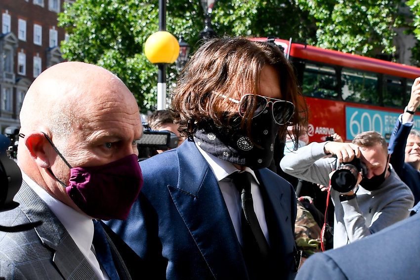 "American actor Johnny Depp (center) wears  protective mask as he arrives at the Royal Court of Justice, in London, Tuesday, July 7, 2020. Johnny Depp has a starring role in a real-life courtroom drama in London, where he is suing a tabloid newspaper for libel over an article that branded him a ""wife beater."" On Tuesday, a judge at the High Court is due to begin hearing Depp's claim against The Sun's publisher, News Group Newspapers, and its executive editor, Dan Wootton, over the 2018 story alleging he was violent and abusive to then-wife Amber Heard. Depp strongly denies the claim.(AP Photo/Alberto Pezzali)"