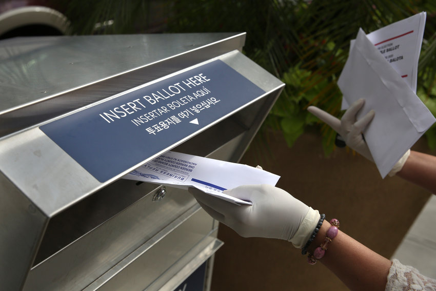 In this July 7, 2020, file photo a woman wearing gloves drops off a mail-in ballot at a drop box in Hackensack, N.J. The November election is coming with a big price tag as America faces the coronavirus pandemic. The demand for mail-in ballots is surging, election workers are in need of training and polling booths might have to be outfitted with protective shields. (AP Photo/Seth Wenig, File)