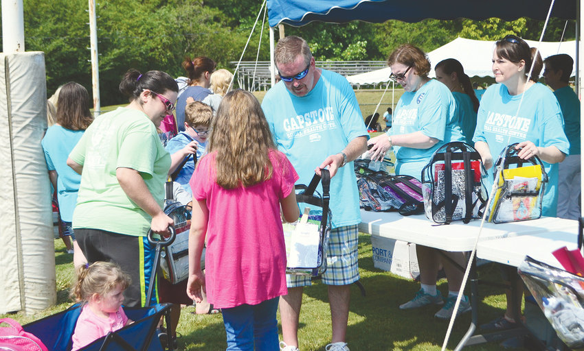 Pictured is a girl receiving a backpack, filled with supplies, at last year's Back 2 School Supply and Backpack Giveaway in Parrish.