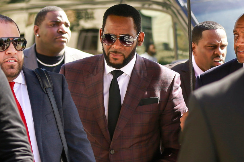 In this June 26, 2019 file photo, R&B singer R. Kelly, center, arrives at the Leighton Criminal Court building for an arraignment on sex-related felonies in Chicago. Federal prosecutors announced charges Wednesday, Aug. 12, 2020, against three men accused of threatening and intimidating women who have accused Kelly of abuse, including one man suspected of setting fire to a vehicle in Florida.  (AP Photo/Amr Alfiky, File)