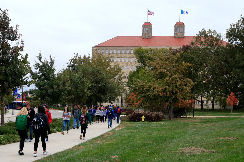 FILE - In this Oct. 24, 2019, file photo students walks in front of Fraser Hall on the University of Kansas campus in Lawrence, Kan. Student loan borrowers with federal debt won't see a bill until January 2021. That means three extra months of paused payments tacked onto the original six months made possible by the coronavirus relief package. (AP Photo/Orlin Wagner, File)