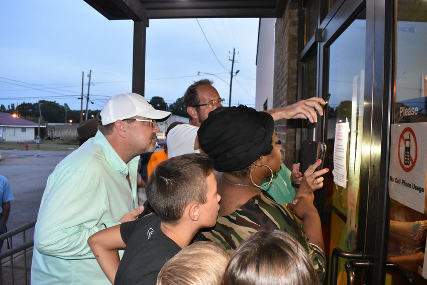 Candidates and citizens crowd the front door of the Carbon Hill Community Center Tuesday night to see the posted results of the municipal elections that day.