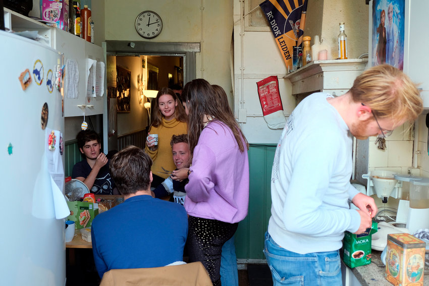 Dutch students chat in the kitchen of their shared house in Leiden, Netherlands on Friday, Sept. 25, 2020. The coronavirus pandemic is hitting students hard in Leiden, the Netherlands' oldest university city. With the virus casting a long shadow over education here and around the world, most lectures are online and the vibrant social life has been reined in to slow the spread of the pandemic. (AP Photo/Mike Corder)