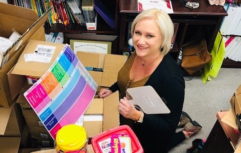 Jasper City Schools curriculum coordinator Kristy Watkins is pictured with some items that will be distributed to students to enhance reading and math skills.