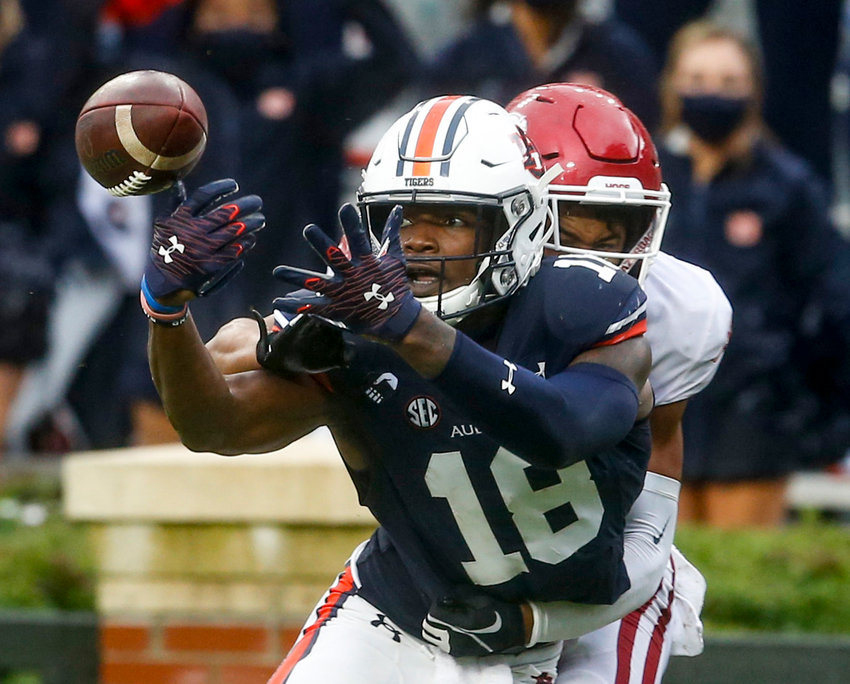 Auburn wide receiver Seth Williams (18) tries to catch a pass as Arkansas defensive back Khari Johnson (19) defends during the second quarter of Saturday's game at Jordan-Hare Stadium in Auburn.