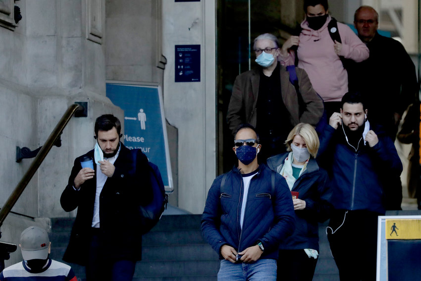People walk down the steps of the main entrance of Waterloo train station, at which point they are allowed to remove their face coverings, in London, Thursday, Oct. 15, 2020. London Mayor Sadiq Khan says he expects the government will move the UK capital to a higher level of COVID-19 restrictions later Thursday. The move comes as infection rates in the capital are rising. Khan says the city will soon reach an average of 100 cases per 100,000, a level some boroughs have already surpassed. (AP Photo/Matt Dunham)