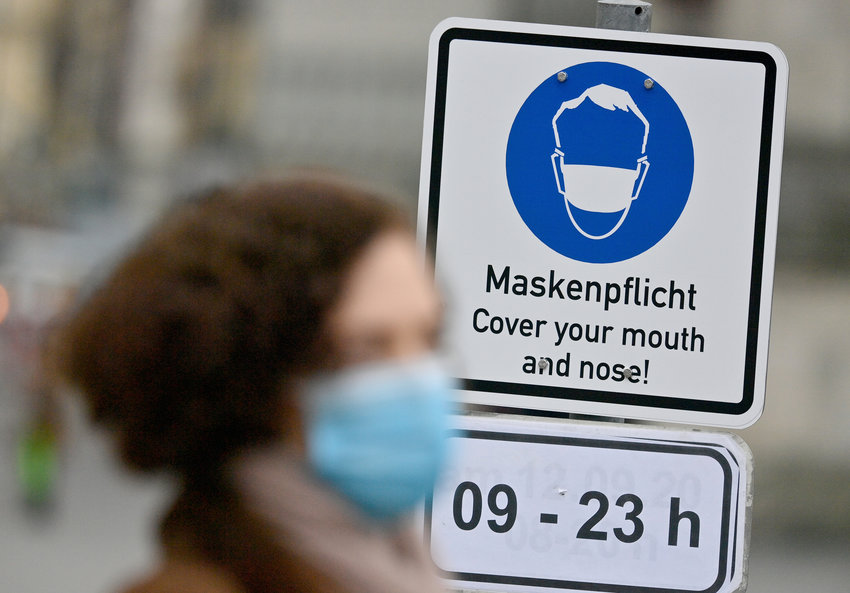 A woman, wearing a face mask, walks past a sign saying 'Mask duty - Cover your mouth and nose!' in a pedestrian zone in the city center of Munich, Germany, Thursday, Oct. 15, 2020. German Chancellor Angela Merkel and Germany's 16 state governors agreed Wednesday night to tighten mask-wearing rules, make bars close early and limit the number of people who can gather in areas where coronavirus infection rates are high. (Peter Kneffel/dpa via AP)