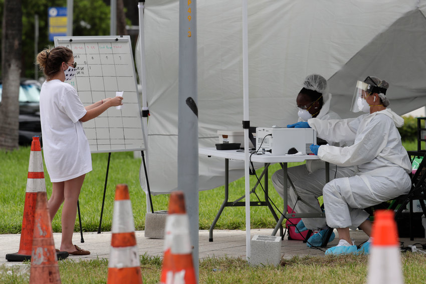 FILE - In this Friday, July 17, 2020 file photo, health care workers take information from people in line at a walk-up COVID-19 testing site during the coronavirus pandemic in Miami Beach, Fla. After months of struggling to ramp up coronavirus testing, the U.S. is now capable of testing some 3 million people daily thanks to a growing supply of rapid tests. But the testing boom comes with a new challenge: keeping track of the results. (AP Photo/Lynne Sladky)