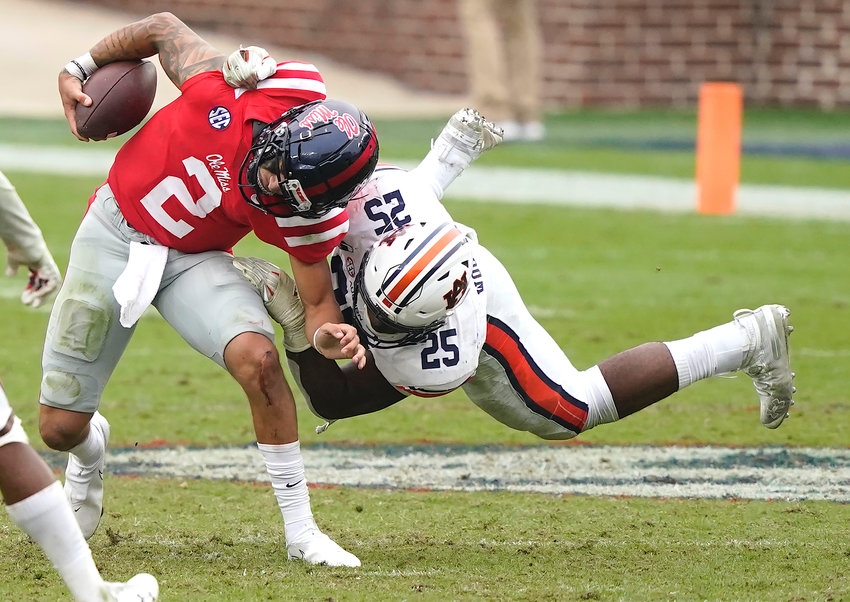 Auburn linebacker Colby Wooden (25) upends Mississippi quarterback Matt Corral (2) during the second half of an their game in Oxford, Miss., Saturday.