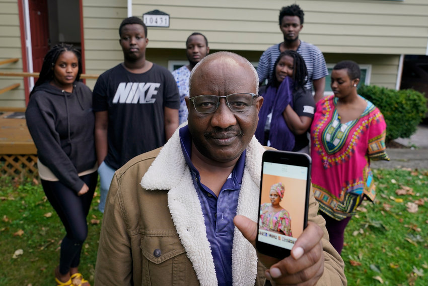 HOLD FOR STORY BY ANITA SNOW AND JULIE WATSON MOVING SUNDAY FOR MONDAY - Sophonie Bizimana, center, a permanent U.S. resident who is a refugee from Congo, poses for a photo, Wednesday, Oct. 14, 2020, at his home in Kirkland, Wash., along with six of his children as he displays a cell-phone photo of his wife, Ziporah Nyirahimbya, who is in Uganda and has been unable so far to join him in the U.S. For decades, America admitted more refugees annually than all other countries combined, but that reputation has eroded during Donald Trump's presidency as he cut the number of refugees allowed in by more than 80 percent. (AP Photo/Ted S. Warren)