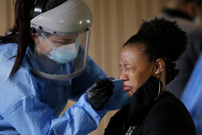 (Mark Lambie/El Paso Times - AP)..Sasha Jacquez tests UTEP student Ariona Gill for coronavirus Friday, Oct. 16, 2020 at the UTEP Fox Fine Arts Center in El Paso.