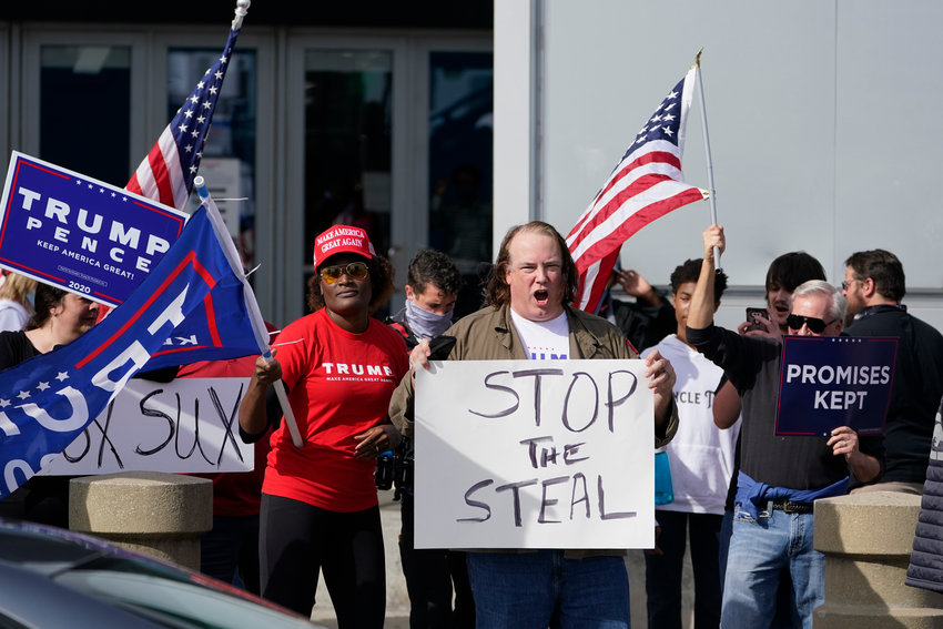Supports of President Donald Trump holds signs during a demonstration outside the State Farm Arena where Fulton County has a voting counting operation, Thursday, Nov. 5, 2020, in Atlanta. (AP Photo/John Bazemore)