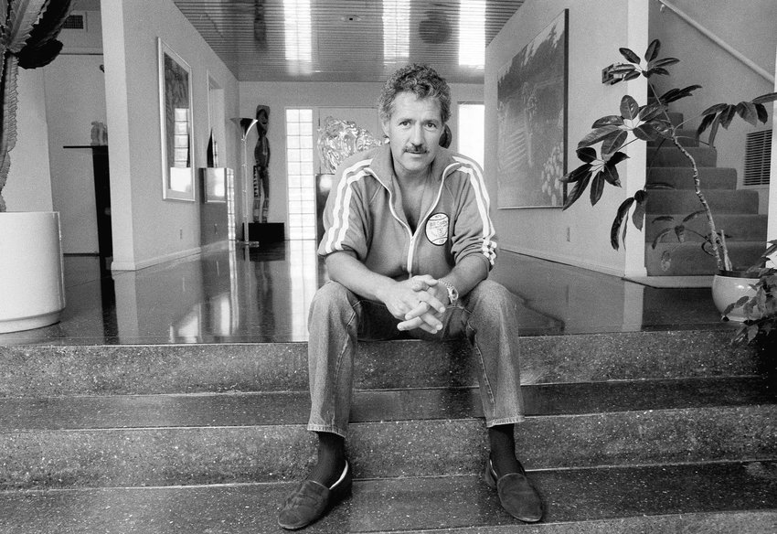 """Game show host Alex Trebek poses for a photo in his Los Angeles home on Aug. 3, 1988. Trebek, who presided over the beloved quiz show """"Jeopardy!"""" for more than 30 years with dapper charm and a touch of school-master strictness,  died Sunday, Nov. 8, 2020. He was 80. (AP Photo/Alan Greth)"""