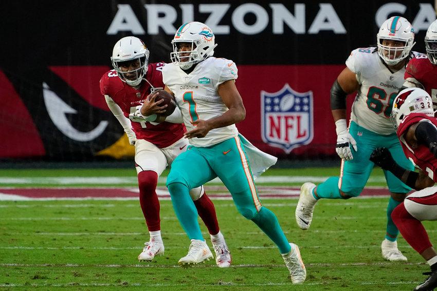 Miami Dolphins quarterback Tua Tagovailoa (1) runs as Arizona Cardinals outside linebacker Haason Reddick (43) pursues during the second half of an NFL football game, Sunday, Nov. 8, 2020, in Glendale, Ariz. (AP Photo/Rick Scuteri)