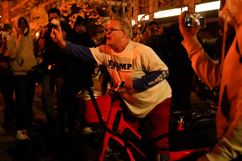A supporter of President Donald Trump sprays a substance as he is surrounded after a pro-Trump march Saturday Nov. 14, 2020, in Washington. (AP Photo/Jacquelyn Martin)