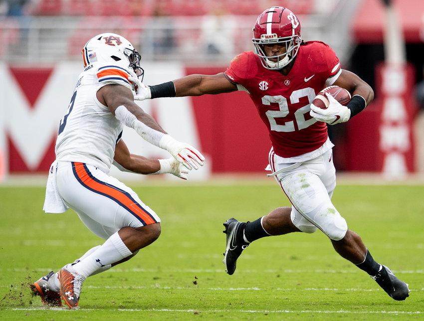Alabama running back Najee Harris (22) stiff arms Auburn linebacker Owen Pappoe (0) during Saturday's Iron Bowl at Bryant-Denny Stadium in Tuscaloosa. Alabama won 42-13.