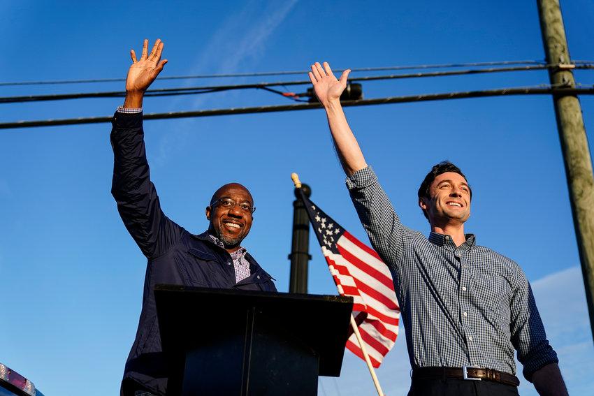 FILE - In this Nov. 15, 2020, file photo Georgia Democratic candidates for U.S. Senate Raphael Warnock, left, and Jon Ossoff, right, gesture toward a crowd during a campaign rally in Marietta, Ga. (AP Photo/Brynn Anderson, File)