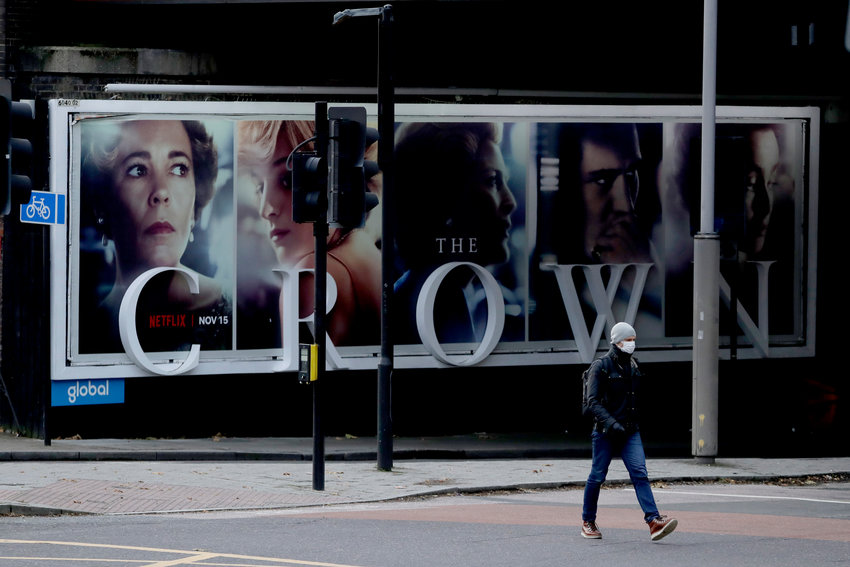 A man wearing a face mask walks past a billboard advertising 'The Crown' television series about Britain's Queen Elizabeth II and the royal family, during England's second coronavirus lockdown, in London, Friday, Nov. 20, 2020. Britain yesterday registered 501 daily COVID-19 deaths within 28 days of a positive test and is the fifth country in the world to record more than 50,000 coronavirus-related deaths. (AP Photo/Matt Dunham)