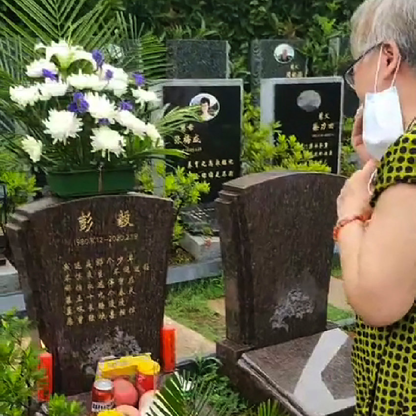 In this photo taken  Aug. 12, 2020 and released by Zhong Hanneng, Zhong Hanneng cries at her son Peng Yi's grave during what would have been his fortieth birthday at a cemetery in Wuhan in central China's Hubei province. Peng had fallen sick with the coronavirus at the beginning of the outbreak on Jan. 23, but because of a shortage of test kits, he wasn't able to get tested for days. His first test result came out negative, barring him access to a hospital bed, and he wasn't able to be hospitalized until weeks later. By then his condition was critical, and he passed away on Feb. 19.  (Zhong Hanneng via AP).