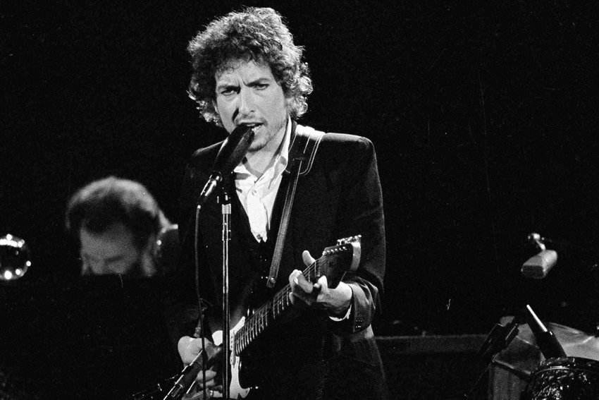 """FILE - In this Feb. 15, 1974, file photo, musician Bob Dylan performs with The Band at the Forum in Los Angeles. Transcripts of lost 1971 Dylan interviews with the late American blues artist Tony Glover and letters the two exchanged reveal that Dylan changed his name from Robert Zimmerman because he worried about anti-Semitism, and that he wrote """"Lay Lady Lay"""" for actress Barbra Streisand. The items are among a trove of Dylan archives being auctioned  in November 2020 by Boston-based R.R. Auction..(AP Photo/Jeff Robbins, File)"""