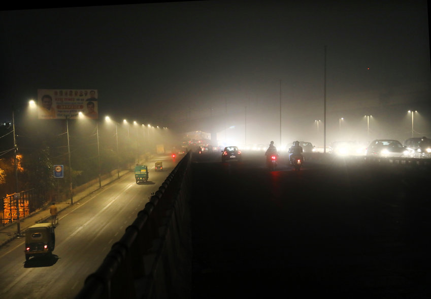 Commuters drive on a road engulfed in smog in New Delhi, India, Thursday, Nov. 5, 2020. India is grappling with two public health emergencies: critically polluted air and the pandemic. Nowhere is this dual threat more pronounced than in the Indian capital New Delhi, where the spike in winter pollution levels has coincided with a surge of COVID-19 cases. (AP Photo/Manish Swarup)