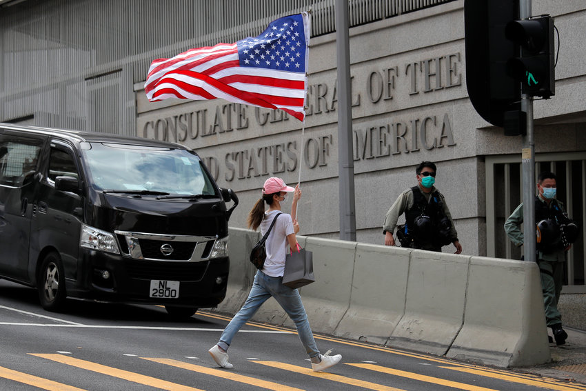 FILE - In this July 4, 2020, file photo, a protester carries an American flag during a protest outside the U.S. Consulate in Hong Kong. China says it is imposing restrictions on travel to Hong Kong by some U.S. officials and others in retaliation for similar measures imposed on Chinese individuals by Washington. (AP Photo/Kin Cheung, File)