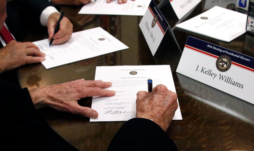 FILE - In this Dec. 19, 2016, file photo members of the Mississippi Electoral College sign certificates of vote in the process of formally casting their electoral votes in the 2016 General Election for President and Vice President of the United States at the Capitol in Jackson, Miss. Presidential electors are meeting across the United States Monday, Dec. 14, 2020, to formally choose Joe Biden as the nation's next president. (AP Photo/Rogelio V. Solis, File)