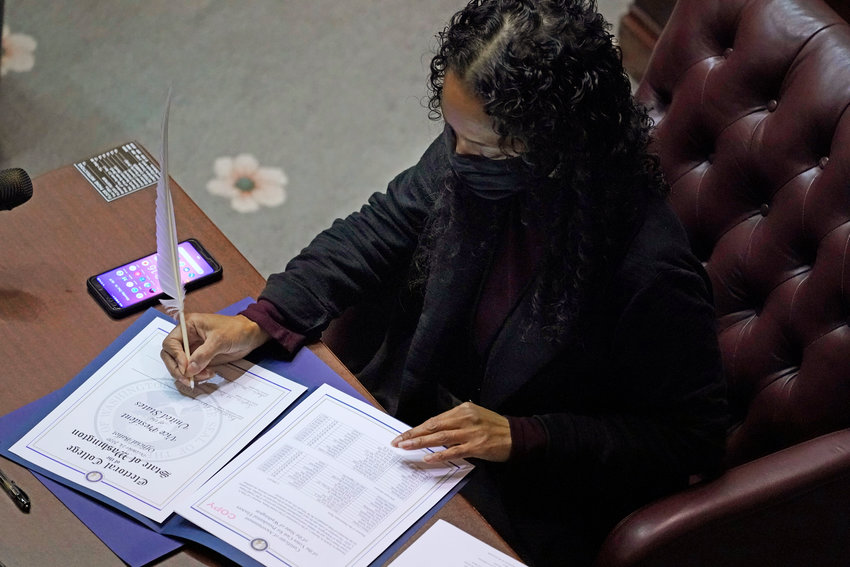 Democrat Sophia Danenberg, a member of Washington's Electoral College, fills in her ballot for Vice President-elect Kamala Harris at the state Capitol in Olympia, Wash., Monday, Dec. 14, 2020. (AP Photo/Ted S. Warren)