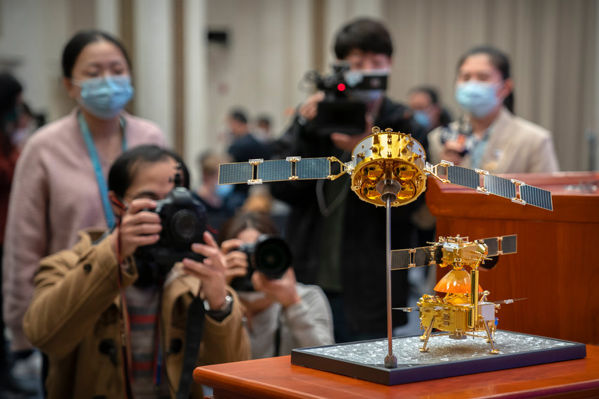 Journalists wearing face masks to prevent the spread of the coronavirus take photos of a model of China's Chang'e 5 lunar orbiter and lander before a press conference at the State Council Information Office in Beijing, Thursday, Dec. 17, 2020. Following the successful return of moon rocks by its Chang'e 5 robotic probe, China is preparing for future missions that could set the stage for an eventual lunar base to host human explorers. (AP Photo/Mark Schiefelbein)