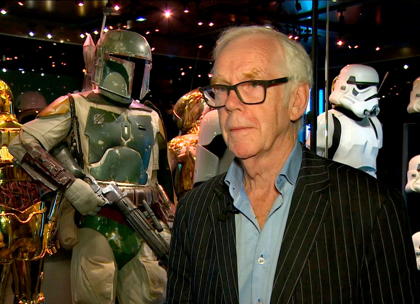 """Jeremy Bulloch speaks while standing in front of the costume he wore while playing Boba Fett in """"Star Wars: Episode V – The Empire Strikes Back"""" and """"Star Wars: Episode VI – Return of the Jedi"""" at the """"Star Wars Identities"""" exhibition in London on July 26, 2017. Bulloch, the English actor who played Boba Fett in the original """"Star Wars"""" trilogy, has died. Bulloch's agents said in a statement that he died in a London hospital Thursday, Dec. 17, 2020, after years of suffering from Parkinson's disease. He was 75. (AP Photo)"""