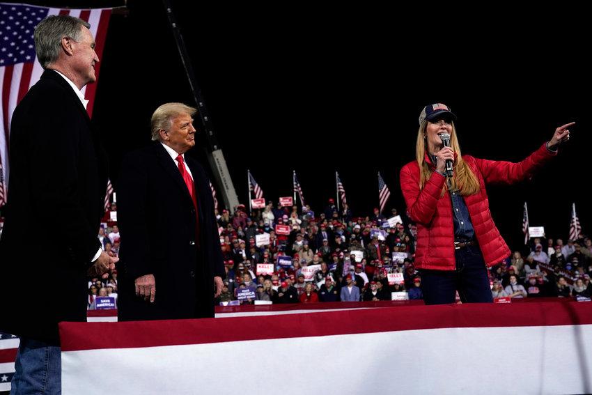 Sen. Kelly Loeffler, R-Ga., speaks as President Donald Trump and Sen. David Perdue, R-Ga., listens at a campaign rally for Senate Republican candidates, Sen. Kelly Loeffler, R-Ga., and Sen. David Perdue, R-Ga., at Valdosta Regional Airport, Saturday, Dec. 5, 2020, in Valdosta, Ga. (AP Photo/Evan Vucci)