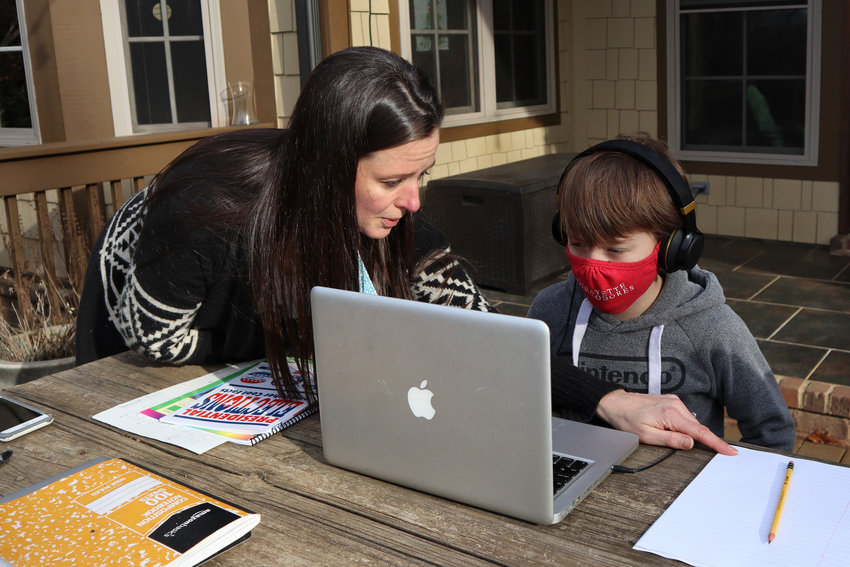 Angela Atkins helps her son Jess Atkins work on a math problem on his laptop during home schooling at their home in Oxford, Miss., on Dec. 18, 2020. Angela Atkins has been homeschooling Jess and his brother, Billy, since October after they struggled with remote learning at their public school. (AP Photo/Leah Willingham)