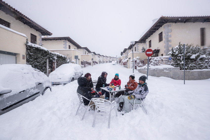 Neighbours have drinks in the middle of the street during a heavy snowfall in Bustarviejo, outskirts of Madrid, Spain, Saturday, Jan. 9, 2021. A persistent blizzard has blanketed large parts of Spain with 50-year record levels of snow, halting traffic and leaving thousands trapped in cars or in train stations and airports that suspended all services as the snow kept falling on Saturday. Half of Spain is on alert, with five provinces on their highest level of warning. (AP Photo/Bernat Armangue)