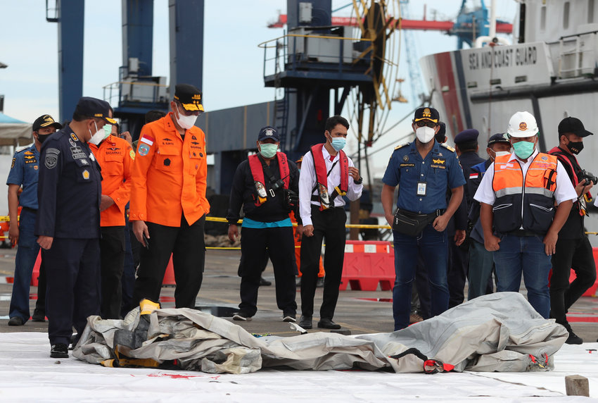 Rescuers inspect debris found in the waters around the location where a Sriwijaya Air passenger jet has lost contact with air traffic controllers shortly after the takeoff, at the search and rescue command center at Tanjung Priok Port in Jakarta, Indonesia, Sunday, Jan. 10, 2021. The Boeing 737-500 took off from Jakarta for Pontianak, the capital of West Kalimantan province on Indonesia's Borneo island, and lost contact with the control tower a few moments later. (AP Photo/Achmad Ibrahim)