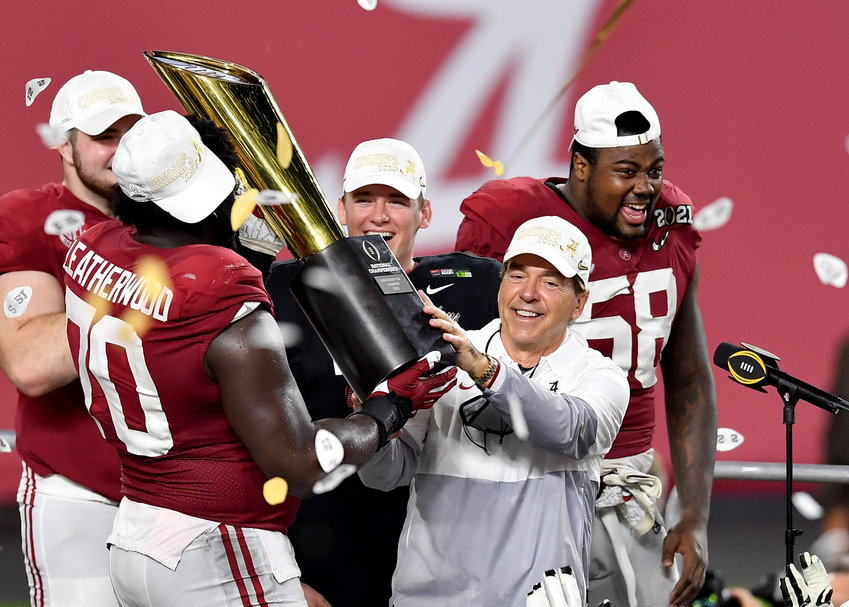 Alabama Crimson Tide head coach Nick Saban and offensive lineman Alex Leatherwood (70) hoist the champion's trophy following Alabama's defeat of the Ohio State Buckeyes at the College Football Playoff National Championship game at Hard Rock Stadium in Miami Gardens, Fla., on Jan. 11, 2021. (Photo by Lee Walls)..